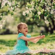 Happy kid girl playing in spring blooming apple garden — Stock Photo #70650823