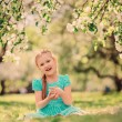 Happy kid girl playing in spring blooming apple garden — Stock Photo #70650829