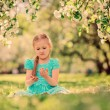 Happy kid girl playing in spring blooming apple garden — Stock Photo #70650831