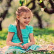 Happy kid girl playing in spring blooming apple garden — Stock Photo #70650835