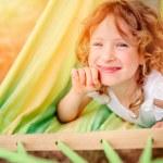 Adorable happy child girl relaxing in hammock in sunny summer garden — Stock Photo #79103988