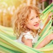 Adorable happy child girl relaxing in colorful hammock in sunny summer garden — Stock Photo #79103994