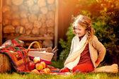 Güneşli sonbahar bahçe içinde kırmızı elma ile beyaz örme Fularlı mutlu çocuk kız — Stok fotoğraf