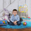 Handsome young boy sitting in Easter scene — Stock Photo #60718171