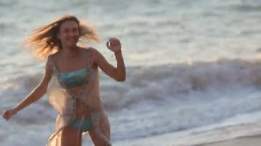 Happy girl runs along the beach and swirls — Stock Video