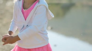 Adorable little girl in bright pink skirt throwing stones into the water of the pond — Stock Video