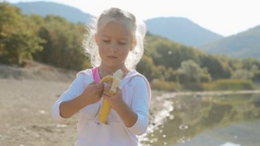 Portrait of little blond girl who eats banana while standing next to lake — Stock Video