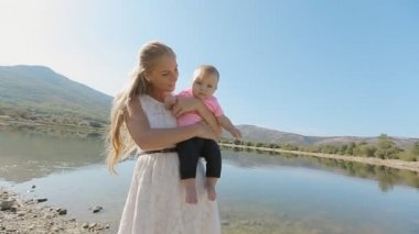 Young mother holds on hands charming baby daughter on background of beautiful mountain landscape — Stock Video