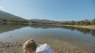 Little girl with ponytail throws stone into lake in slow motion — Stock Video