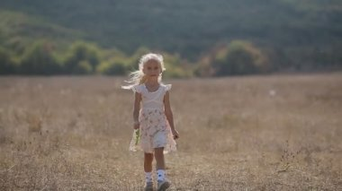 Thoughtful little girl goes on meadow in slow motion — Stock Video