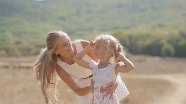 Young beautiful mother kissing little daughter and circling her in slow motion — Stock Video