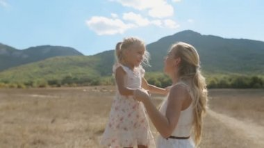Mom having fun with a young daughter, they kiss and hug each other on background of mountain slopes — Stock Video