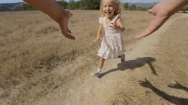 Carefree little girl is twirled around by father in the field — Stock Video