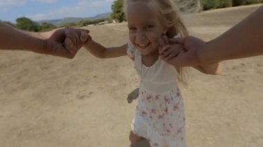 Carefree little girl is whirled by father in the field in slow motion — Stock Video