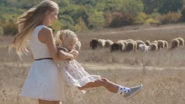 Young mother whirling her little daughter next to the flock of sheep in slow motion — Stock Video