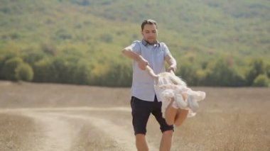 Carefree little girl is whirled by father in the field — Video Stock