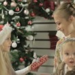 Stylish mother with two young daughters sitting next to beautiful Christmas tree — Stock Video #61058957