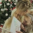 Beautiful young mother sitting with two adorable little girls and reading book — Stock Video #61059081