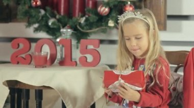 Little blond girl with long hair and wearing a red sweater with snowmens shakes Christmas gift — Stock Video