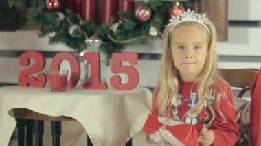 Amazing little girl with blue eyes and long white hair sits near a Christmas tree with box-gift and smiling — Wideo stockowe