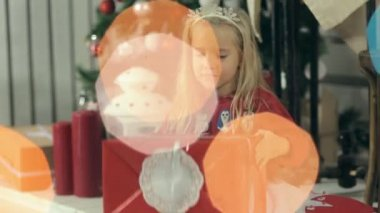 Incredibly beautiful little girl looks at a gift in a red package near the Christmas tree and presents it by her mom — Stock Video