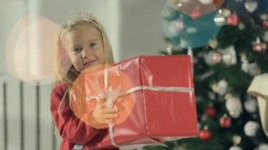 Cute little girl stands near stylishly decorated Christmas tree with a big gift box packed in red paper — Stock Video