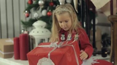 Funny little blonde girl with long hair sitting near a beautifully decorated Christmas tree and examines a big box with a gift — Stock Video