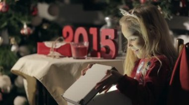 Cute little girl with long hair wearing in sweater with snowmen opens a box with magic in the dark on the new year — Stock Video