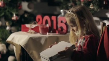 Incredibly cute little girl sitting in the dark near decorated Christmas tree and slowly opens the box with a New Years miracle inside — Stock Video