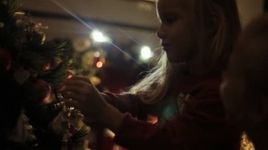 Mom takes the little girl Christmas toys and together they decorate a Christmas tree — Stock Video