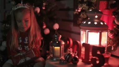 Incredibly cute little girl with long hair and rim sits next to a glowing lantern and looks at a gift — Stock Video
