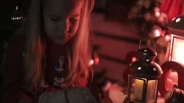 Beautiful little girl looking at a gift in a red package while sitting near Christmas tree — Stock Video
