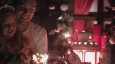 Happy family with two charming children greeted the new year by lighting sparklers — Stock Video