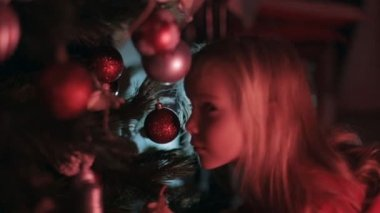 Amazing little girl with long blond hair sitting near the Christmas tree decorated with balls — Stock Video