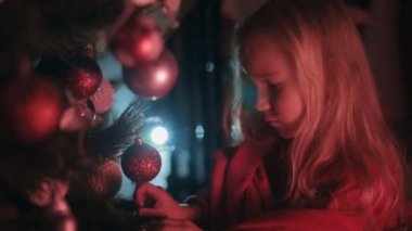 Beautiful little girl hangs on the Christmas tree Christmas balls — Wideo stockowe