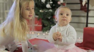 Little girl with long blond hair with her kid sister near Christmas tree — Stock Video