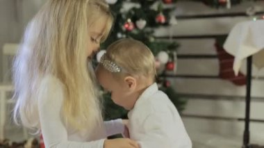 Cute little girl playing with her baby sister near Christmas tree — Stock Video