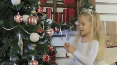 Little beautiful girl with long blond hair decorates the Christmas tree — Stock Video
