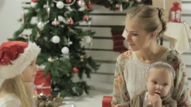 Young mother with two lovely girls sitting by the decorated Christmas tree — Stock Video
