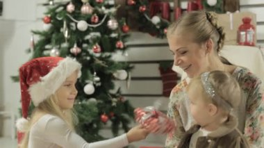 Family of three sitting by the Christmas tree in the beautifully decorated interior — Stock Video