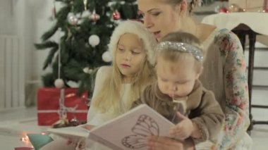 Young mother reading a story to their adorable little daughter — Video Stock