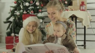 Beautiful mother reads fairy story to her little daughters — Wideo stockowe