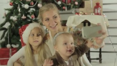 Charming mom with two lovely daughters makes the photo on phone — Stock Video