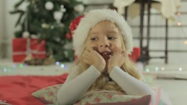 Cute little girl in Santas hat lying on the pillow near Christmas tree — Stock Video