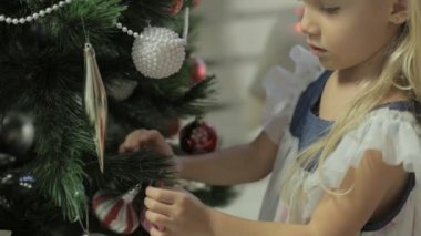 Little lovely girl in beautiful dress decorates Christmas tree — Stock Video