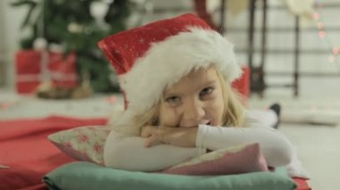 Adorable little girl blonde lies on the pillow in Santas hat — Stock Video