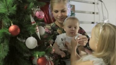 Little cute girl in a beautiful dress with long blond hair decorates a Christmas tree — Stock Video