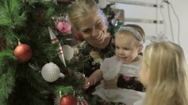 Beautiful little girl with her mother and younger sister decorating a Christmas tree — Stock Video