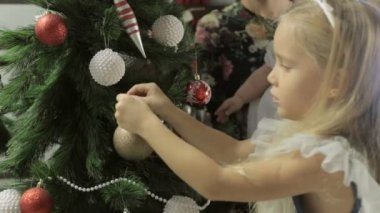Cute little girl with long hair and beautiful headband  decorates a Christmas tree with baubles — Stockvideo