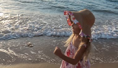 Young mother with her little daughter running to father with baby in his arms along the beach in slow motion — Stock Video